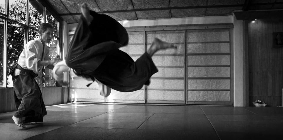 Una persona aplicando una tecnica de aikido a otra en un dojo