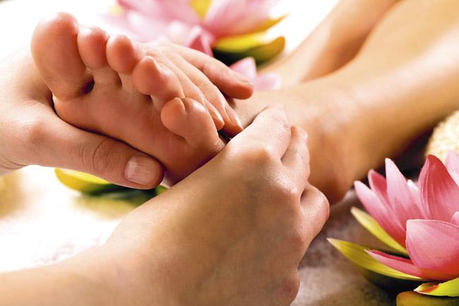 manos haciendo terapias de reflexologia podal